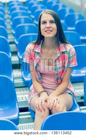 The girl is sitting alone in the cinema hall