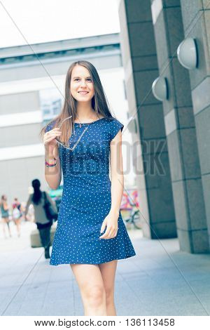 Pretty girl with long hair wearing a short dress in the city. Toned photo