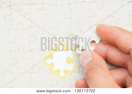 Closeup of hand placing the last jigsaw puzzle piece conceptual of problem solving finding a solution.