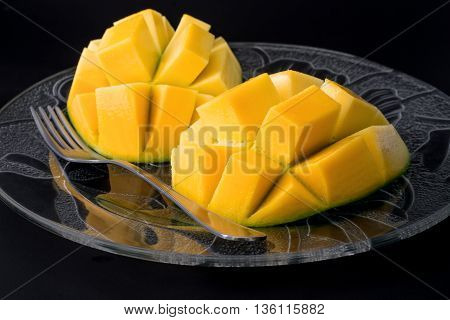 A sliced mango on a glass plate with a fork and black background