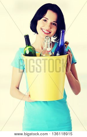 Beautiful young woman holding recycling bin
