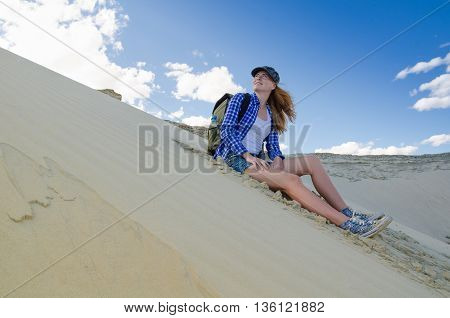 Young beautiful woman backpacker traveling in the desert. Sandy dunes and blue sky on sunny summer day. Travel adventure freedom concept. Toned.