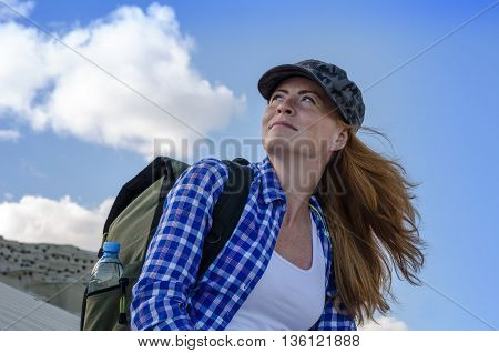 Young beautiful woman backpacker with red hair and freckles traveling in the desert. Sandy dunes and blue sky on sunny summer day. Travel adventure freedom concept. Toned.