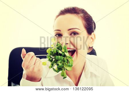 Beautiful business woman sitting and eating lettuce.