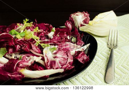Vegetable salad with endive and fennel fresh and healthy on dark wooden background with fork. Vegetarian Food. Healthy food. Dietary meal. Selective focus.