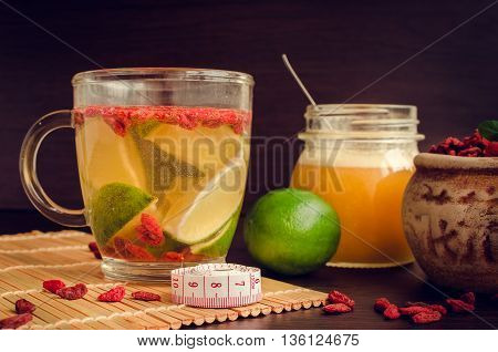 Cup of delicious dietary Goji berry tea with lime and honey on wooden background with measuring tape. Wolfberry for a healthy diet. Alternative medicine. Recovery. Rejuvenation. Slimming.