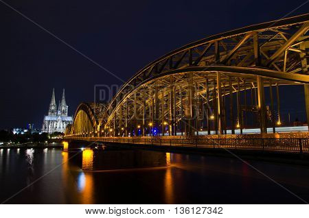 Cologne, North Rhine-Westphalia, Germany - June 11, 2016: View of Cologne Cathedral and Hohenzollern bridge at night.