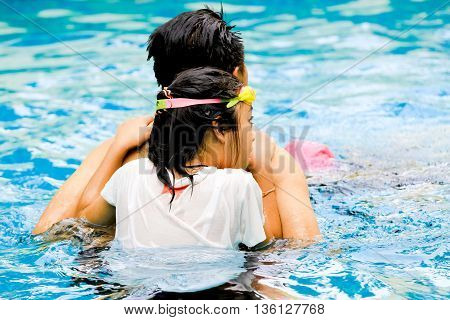 love and care concept : girl in swimming behind her father