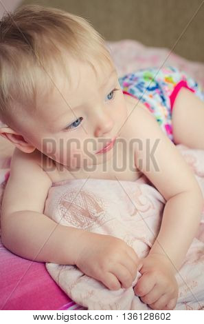 Adorable naked baby boy with big blue eyes lying on the bed. Cute toddler in pink diaper lying on his stomach on the pink sheet and looking aside. Beautiful baby is lying on a bed.