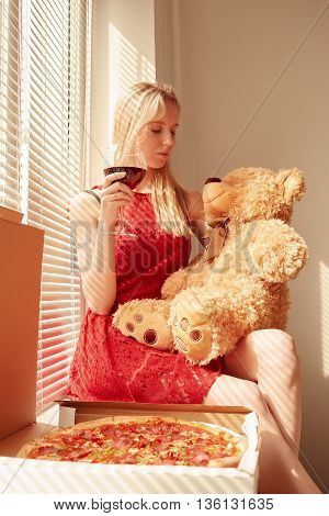 blond girl with teddy bear drinking wine with pizza