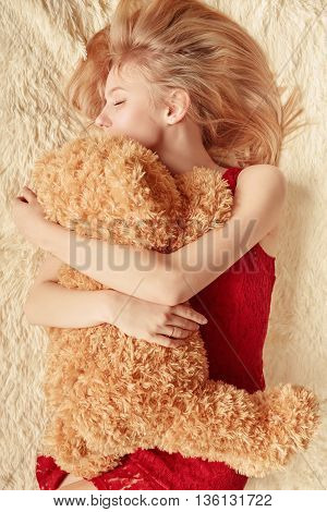 blond girl lying with teddy bear toned image