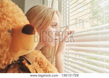sad girl with teddy bear looking in window