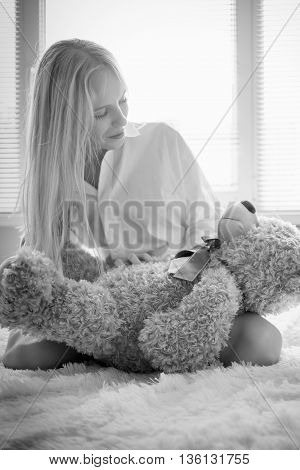 sensual girl sitting with teddy bear in sun light monochrome image