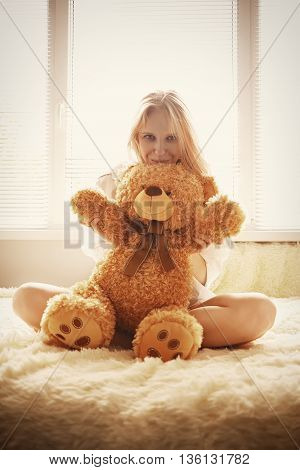 sensual girl sitting with teddy bear toned image