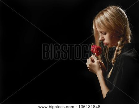 sensual blond girl with rose on black background with copyspace