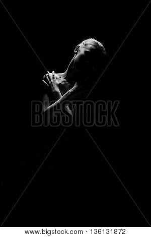 sad woman sitting in dark monochrome image with copyspace