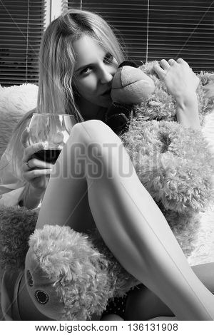 sensual girl with wine and teddy bear looking at camera monochrome