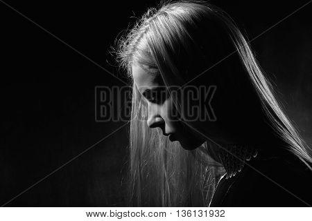 sad pensive girl profile on black background monochrome image