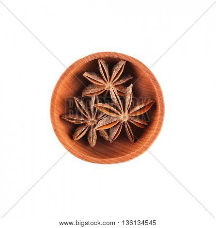 Star anise spice in small wooden bowl isolated on white