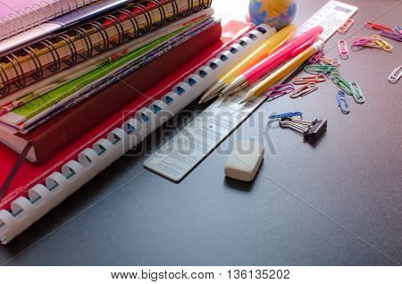 School supplies on blackboard background. Back to school concept with space for text. Notebook stack pens and pencil. Schoolchild and student studies accessories. Back to school concept. Toned image.