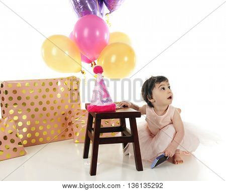 An adorable one year old looking up as she sneaks a cell phone during her birthday celebration.  On a white background.