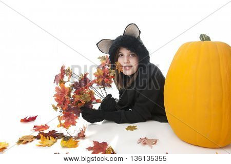An attractive teen girl laying belly-down in her black-cat outfit.  She's laying behind a large orange pumpkin and holds a paw full of colorful fall leaves.  Isolated on white.