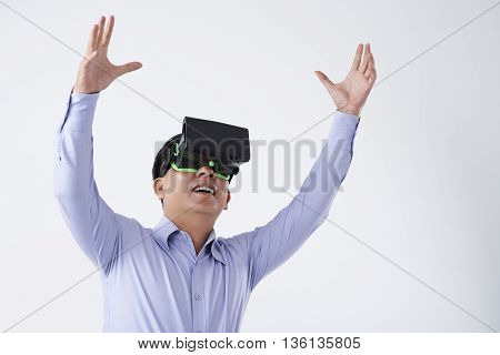 Asian businessman in VR goggles enjoying new technology