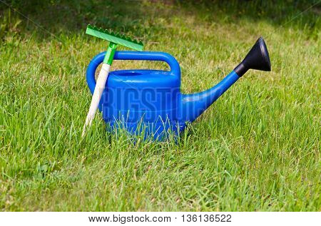 Blue plastic watering can and small rake on the background of green grass in summer in the garden outdoors. Bright equipment for garden care.