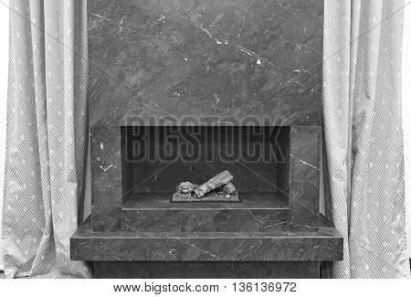 Minimalism stone fireplace. Apartment interior detail. Black white