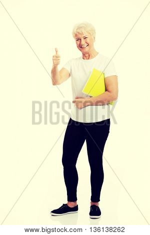 An old woman holding workbook and showing OK.