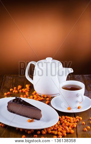 white tableware cup kettle plate chocolate dessert and berry sea buckthorn  on wooden background beautiful dish
