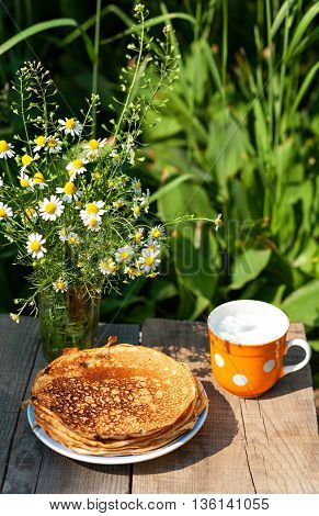 Bouquet of daisies, pancakes and glass of milk on a wooden table. Pancakes and milk, a delicious and healthy breakfast.