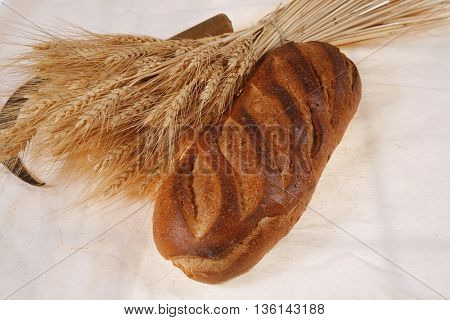 bunch of mown wheat ears with vintage handmade reaper hook sickle and rye dark white french fresh bread loaf on light linen tablecloth