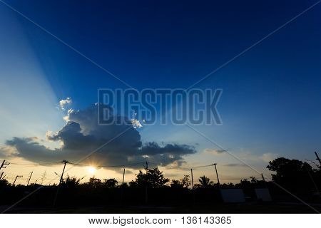 Beam Of Sunlight Through Cloud On Sunset Sky With Silhouette Landscape