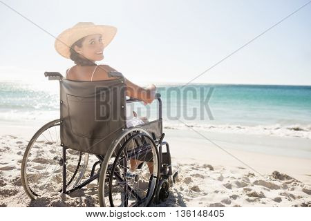 Wheelchair woman sitting smiling at camera on the beach