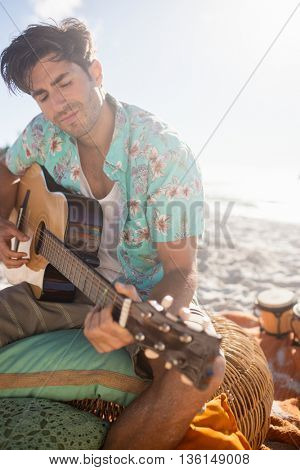 Man playing the guitar on the beach