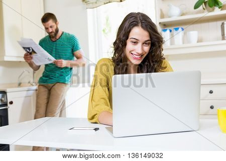 Woman using laptop while man reading newspaper in background at kitchen