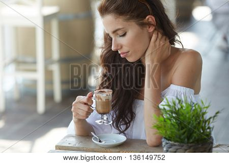 Portrait of beautiful blond woman sitting in outdoors cafe in Italy, drinking coffee