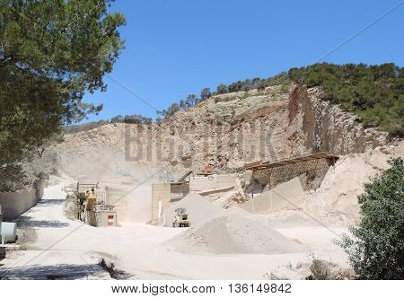 Stone quarry with blue sky and construction machinery.