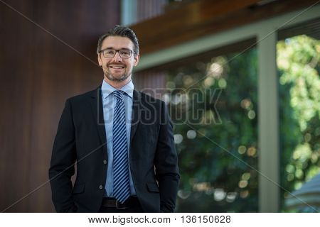 Portrait of happy businessman standing in resort