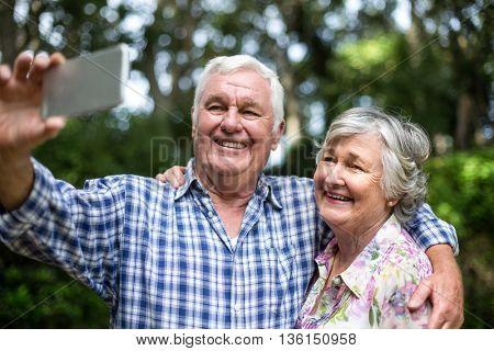 Cheerful senior couple taking selfie through smart phone in back yard