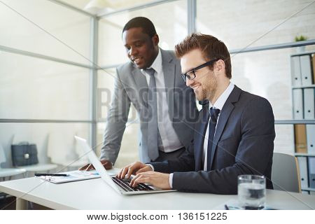 Male colleagues watching documents on laptop