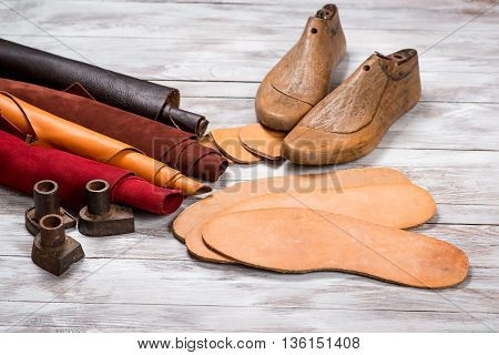 Set of leather in rolls, craft tools on the white wooden background. Workplace for shoemaker. Working handmade tools on a work table.