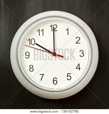 'Beginning of workday' or 'time' concept: a photo of a typical white office clock on a dark background
