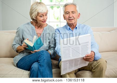 Senior couple reading newspaper while sitting on sofa at home