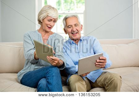 Smiling senior couple using digital tablet while sitting on sofa at home