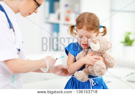 Doctor holds an injection vaccination the child