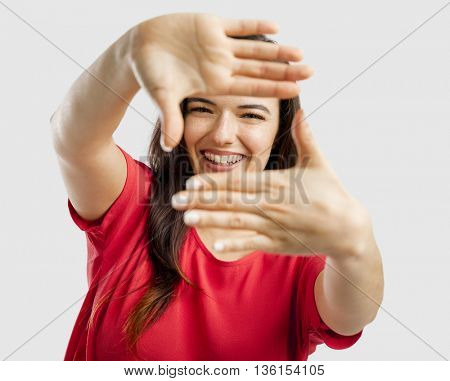 Portrait of a lovely woman framing her face with her hands and smiling