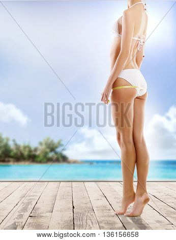 Sexy girl measuring perfect body. Summer beach background. Fat lose, sport and fitness concept.