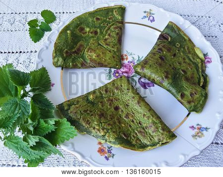 Green nettle pancakes cooking vegetarian healthy food with wild plants